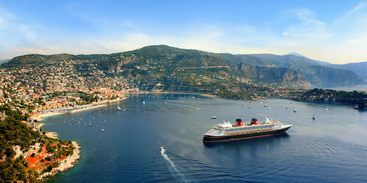 The Disney Magic cruise ship anchored off a coastal town on the Mediterranean Sea