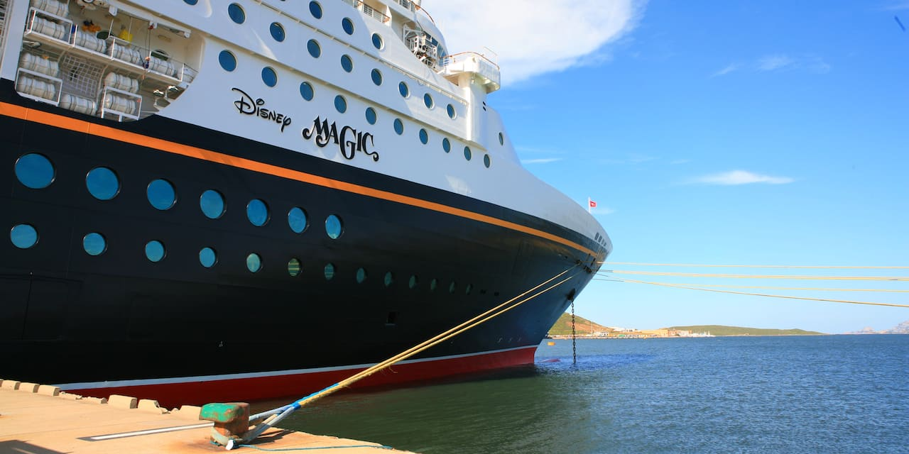 The side of the Disney Magic cruise ship which is tethered to a dock