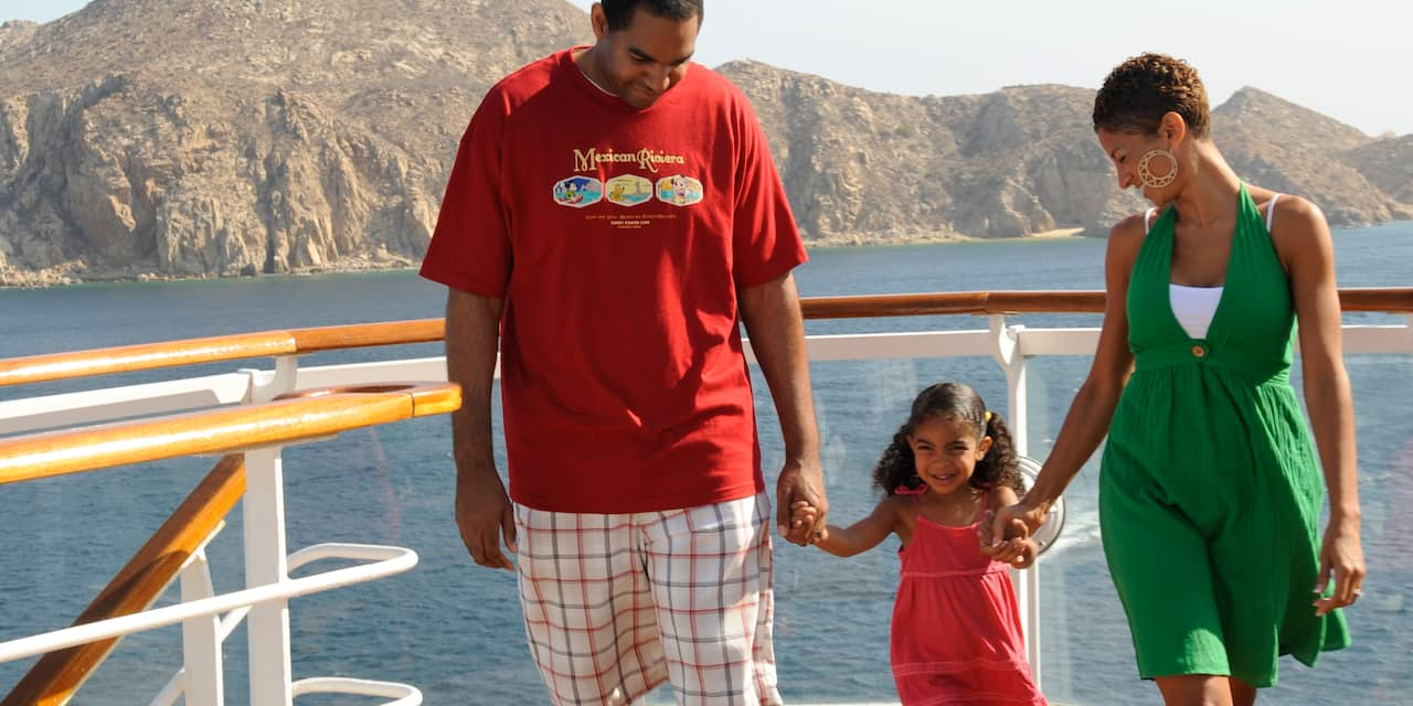 A man and woman hold their young daughter's hands as they walk on a deck of a ship with a mountain in the background