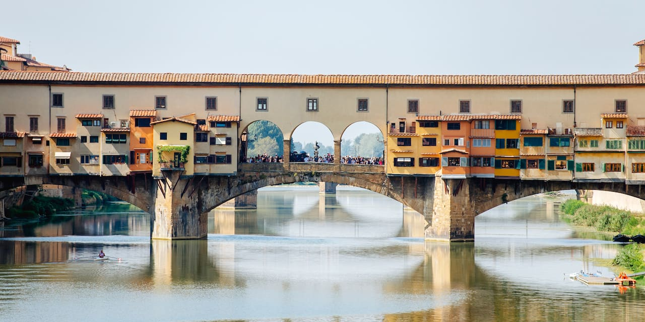 The shop-lined Ponte Vecchio bridge with stone arches spans the Arno River in Florence, Italy