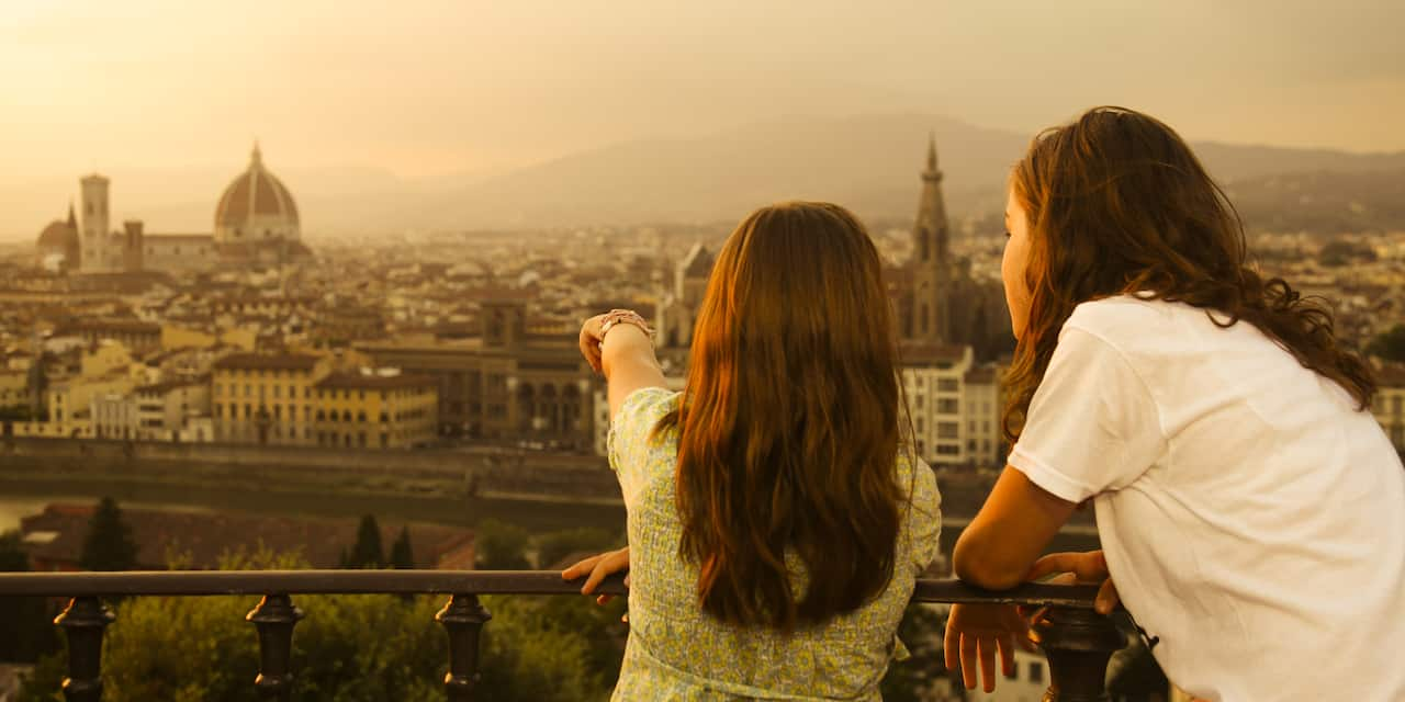 2 girls look from a balcony at the city of Florence, Italy