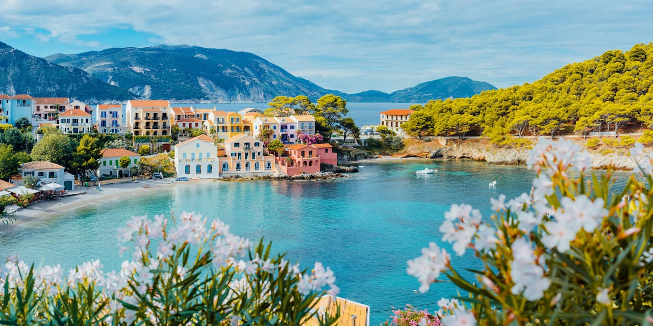 Colorful buildings along the shore of a bay in Kefalonia, Greece with mountains and a sea in the background