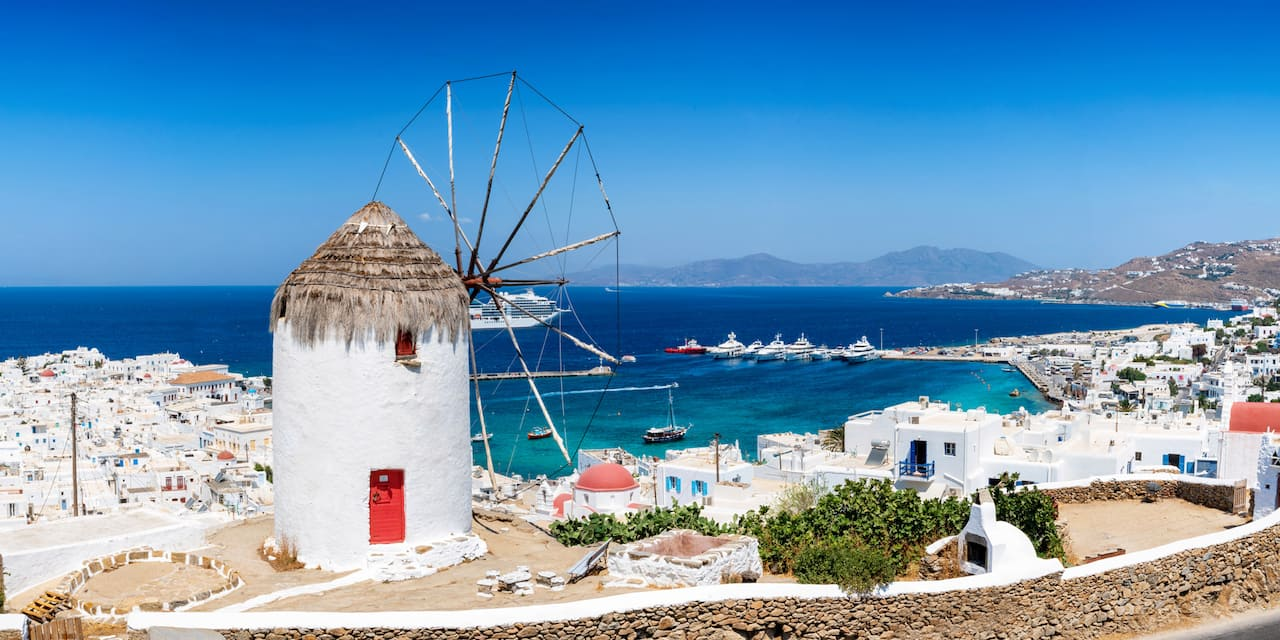 A windmill with a thatched roof in a sea-side town on the Greek island of Mykonos