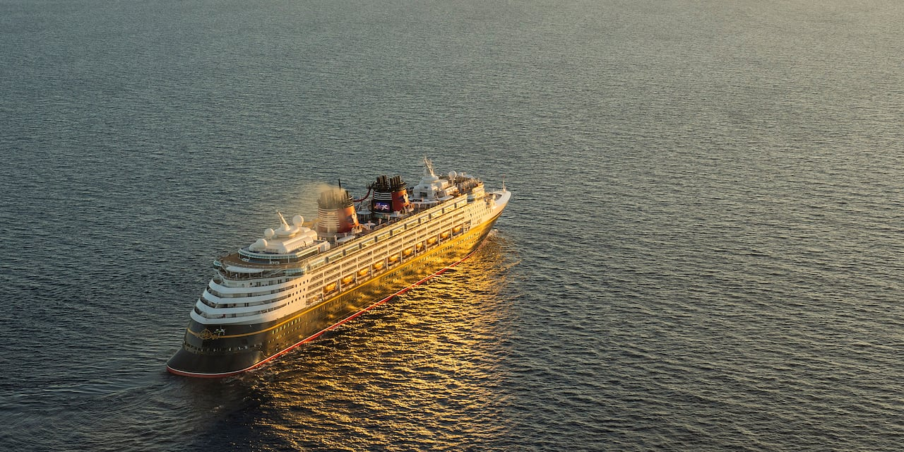 A Disney Cruise Line cruise ship sails on the sea towards the horizon