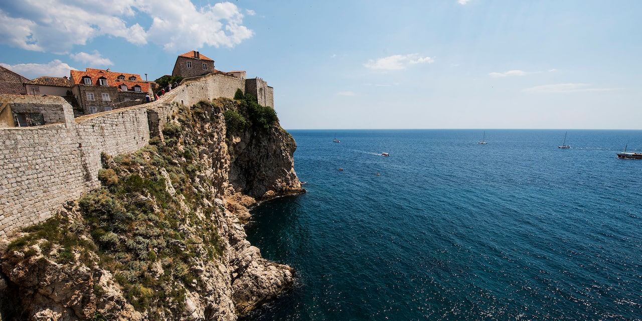 Buildings behind a stone wall sit atop a cliff overlooking the Adriatic Sea
