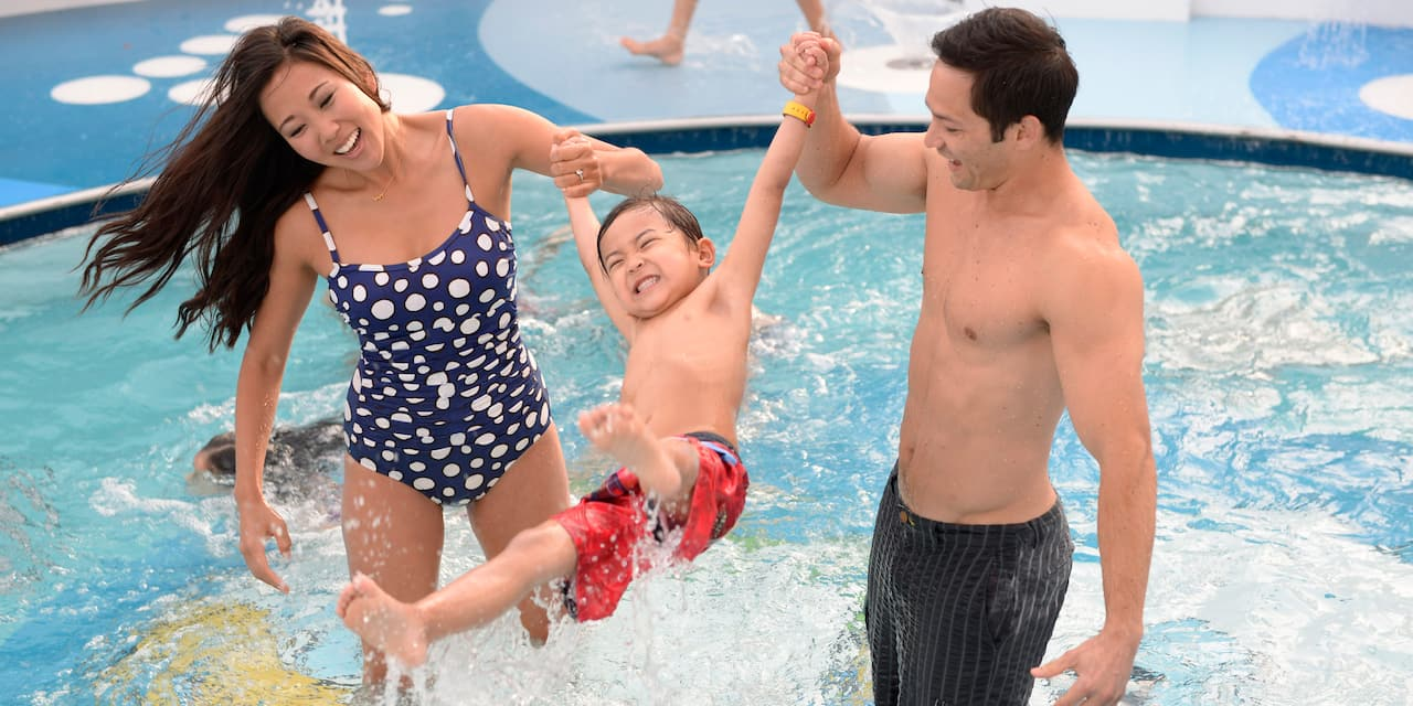 A man and a woman in bathing suits swing their son as they play in a pool on the Disney Magic cruise ship