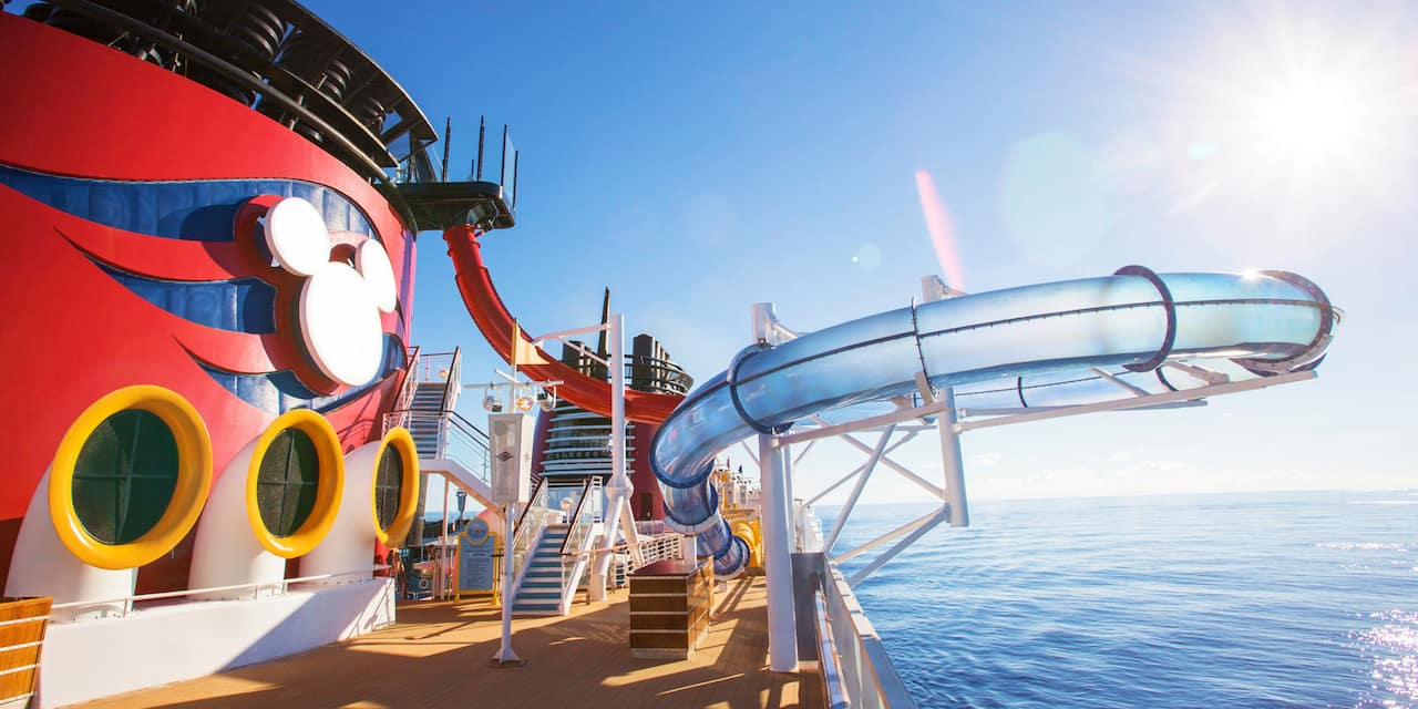 The top deck of the Disney Magic cruise ship with the AquaDunk water slide extending over the ocean and the Mickey Mouse logo on the ship's Forward Funnel