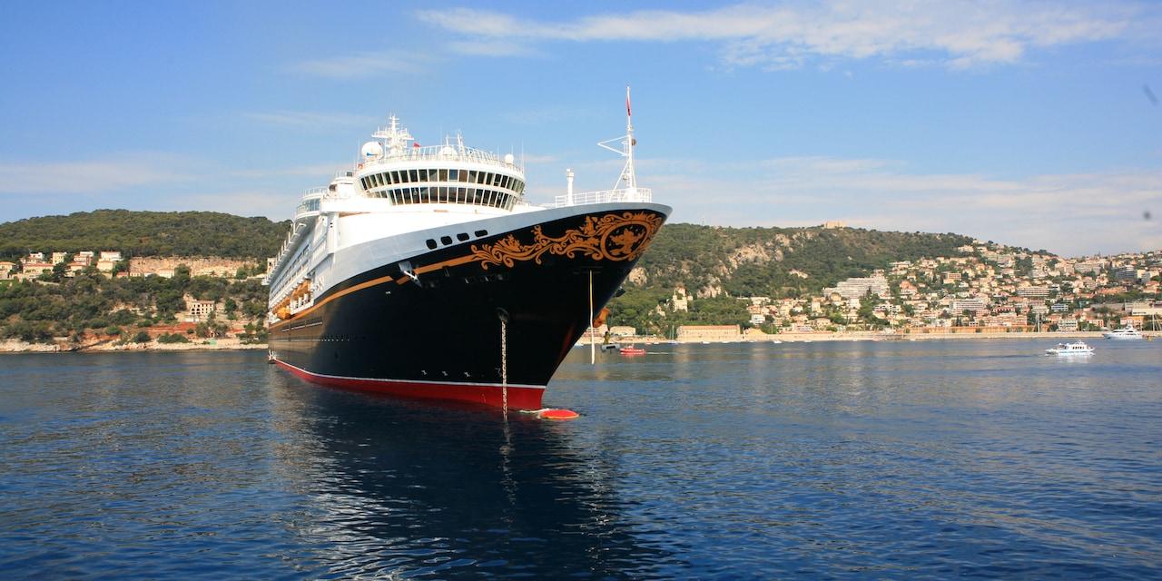 The Disney Wonder cruise ship anchored off a nearby coastline