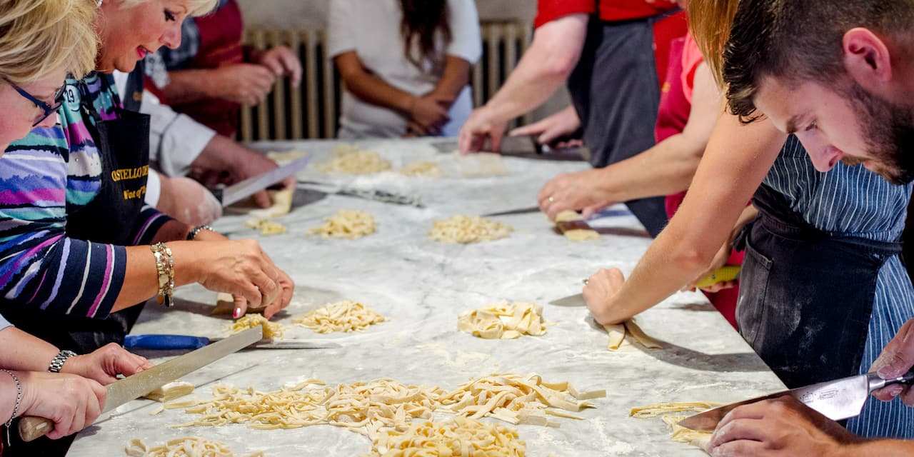 A group in a cooking class utilize kitchen utensils and ingredients on a table as an instructor watches from the head of the table
