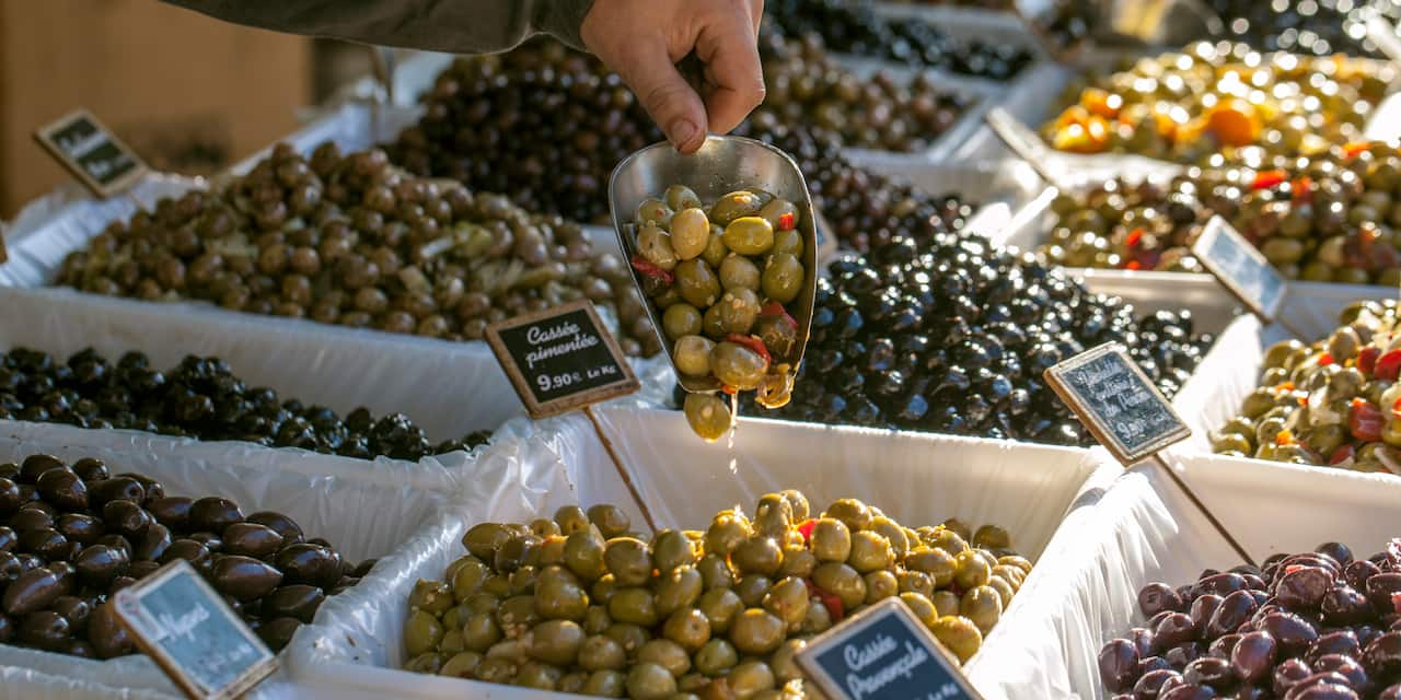 A hand holds a scoop full of olives taken from one of many olive bins at a market