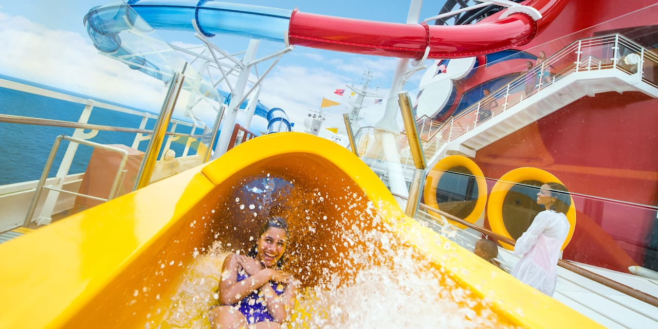 A smiling young woman with her arms crossed rides down the AquaDunk body slide on the Disney Magic cruise ship