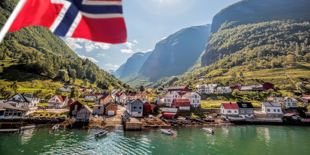 Houses line a quiet bay with a Norwegian flag visible