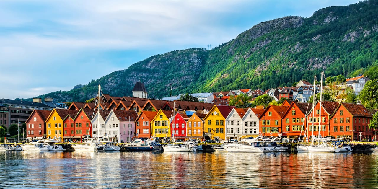 Row of colorful houses line a bay with boats