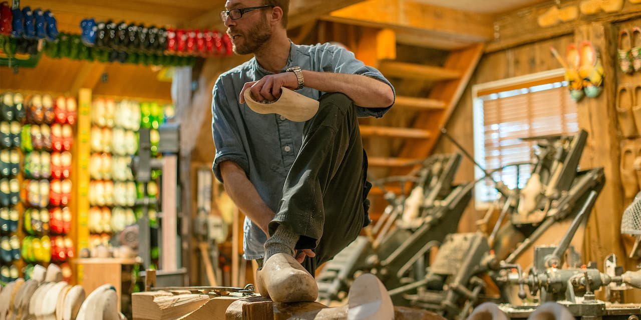 A man wearing glasses stands in a wooden shoe shop holding a clog that he is preparing to paint