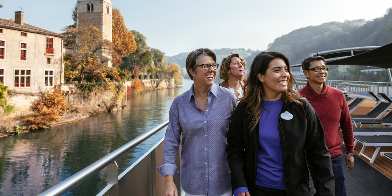 An Adventure Guide and 3 Adventurers pass a stone building and tower as they sail down the Rhône Rive