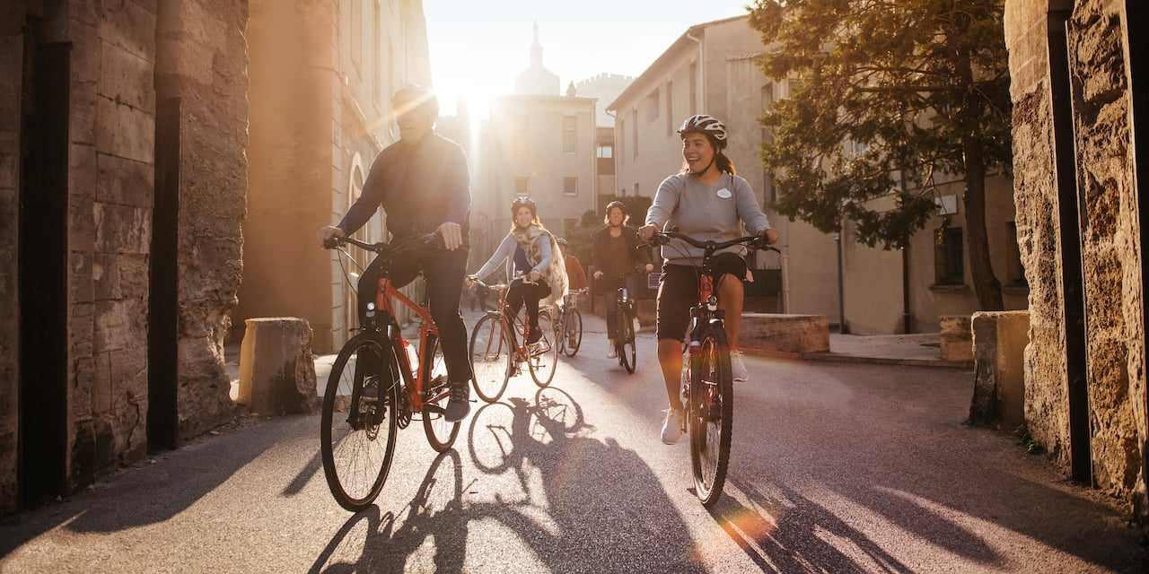 An Adventure Guide and several Adventurers ride bikes on a street in Lyon, France