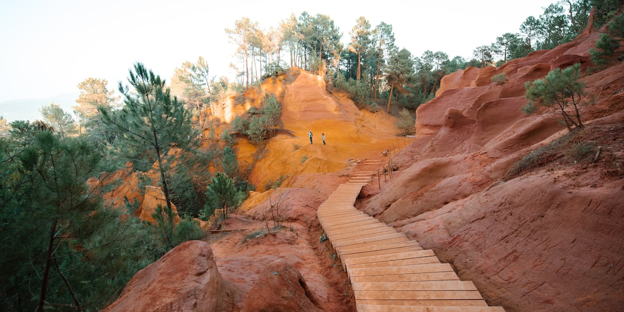 Wooden steps lead down the Ochre Trail where a couple stand in the distance