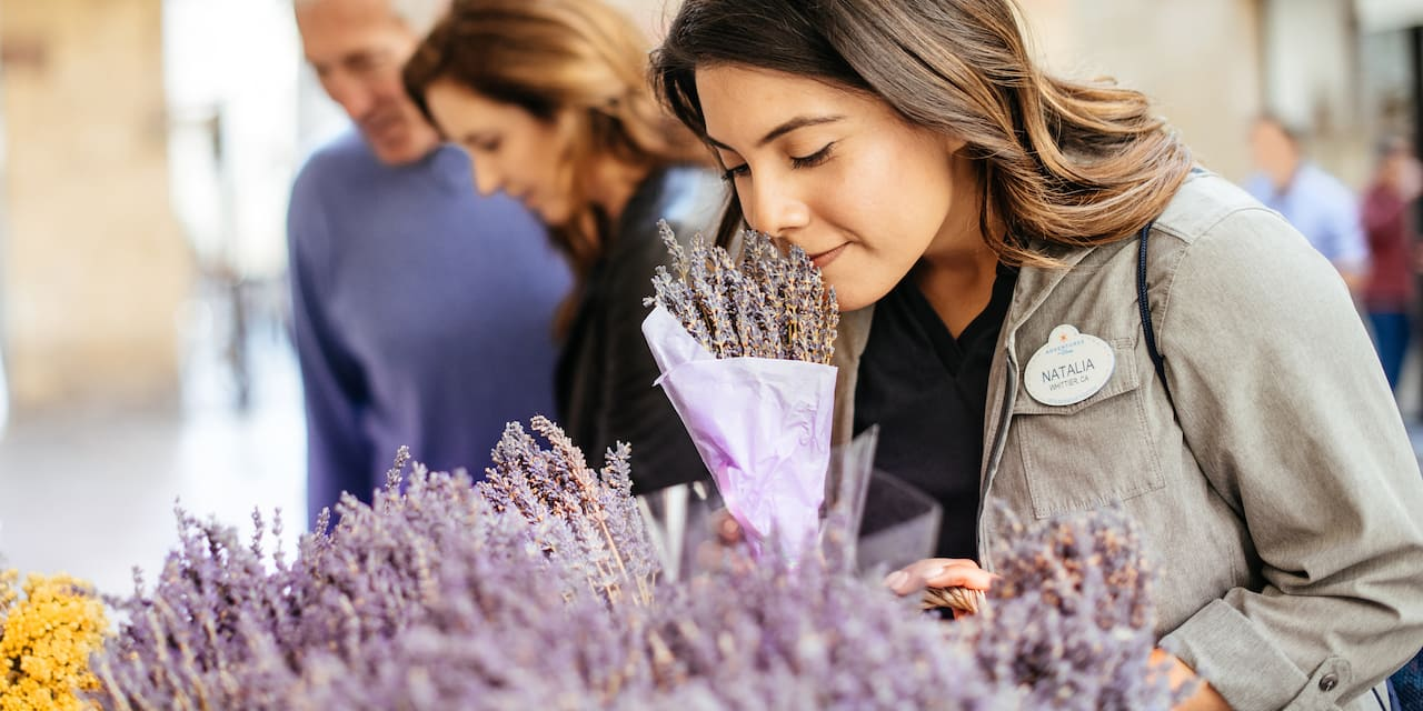 An Adventure Guide smells a batch of lavender