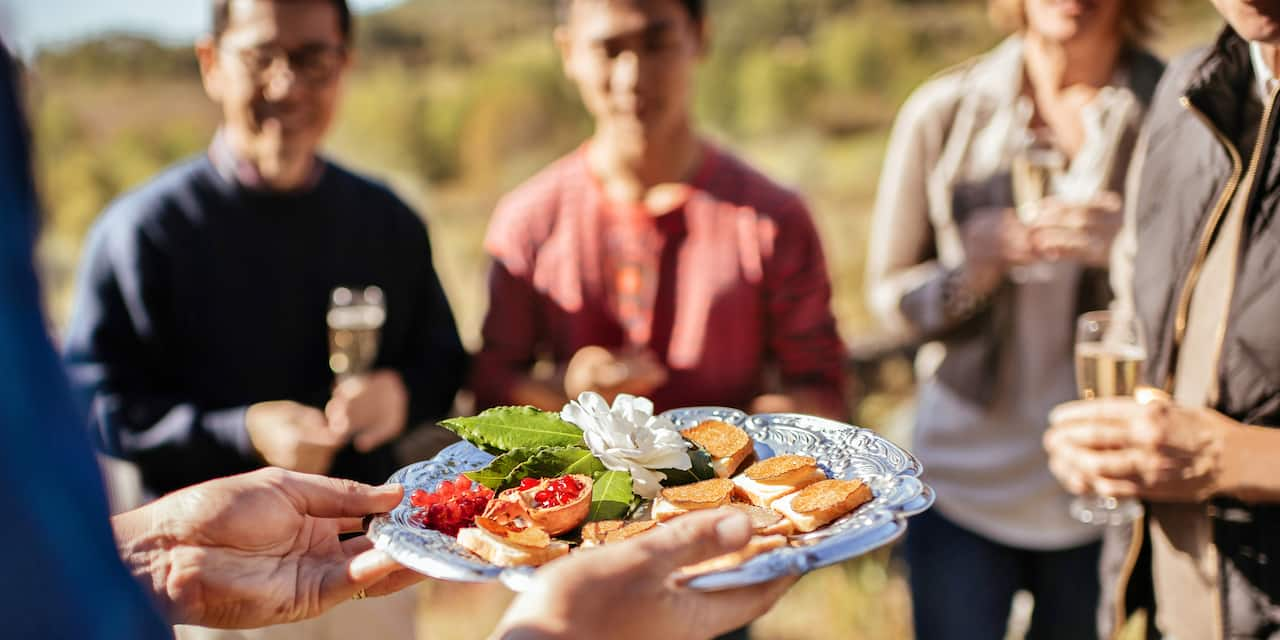 A plate of crackers and other foods, decorated with a flower, is presented to a group of people, each holding a glass of wine