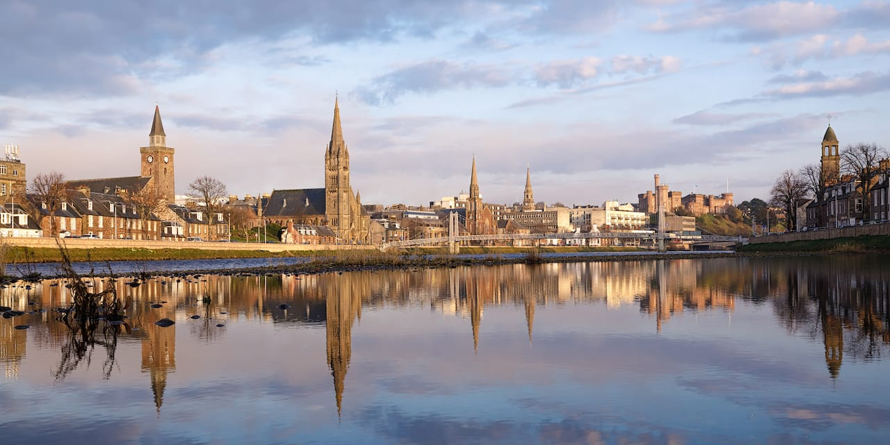 The city of Inverness, with steepled buildings reflected on the water of the River Ness