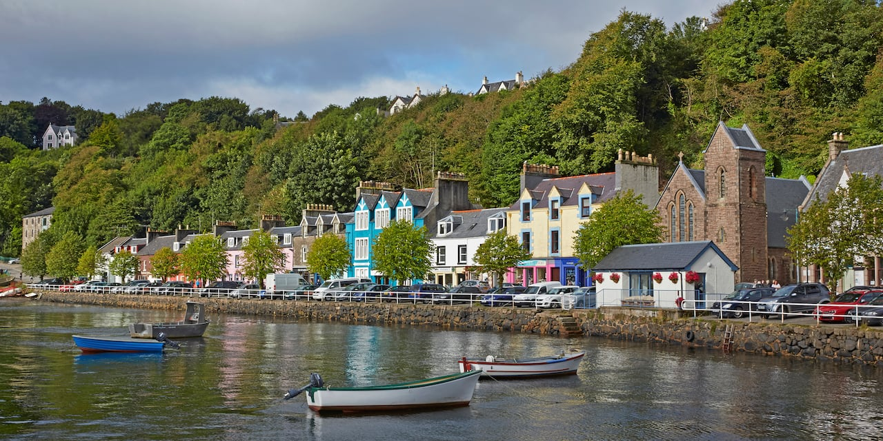 A row of houses along a street between a forest of trees and the Caledonian Canal where several boats are anchored.