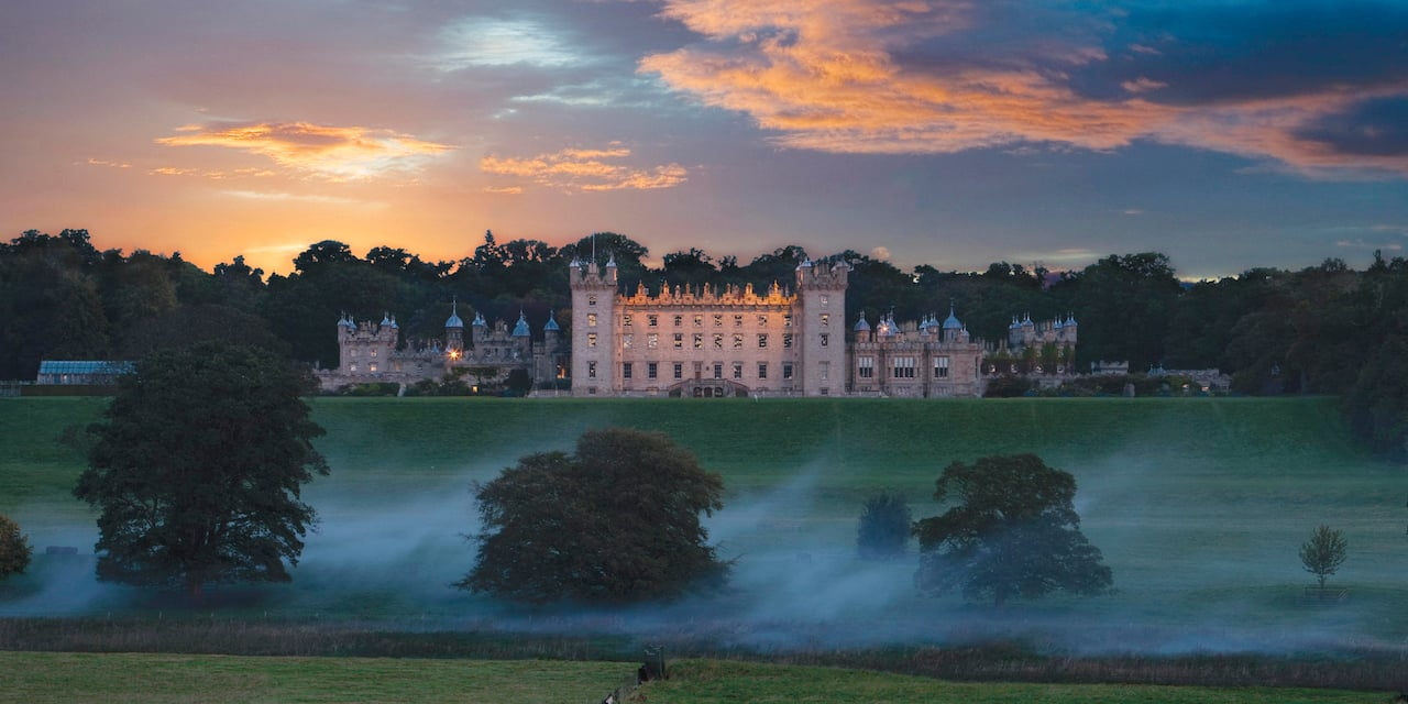 The majestic Floors Castle sits perched atop a grassy plateau as a hot air balloon hovers nearby