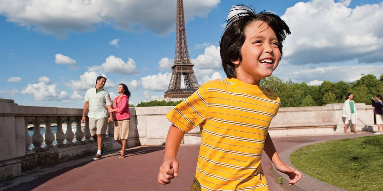 A young boy runs ahead of his parents with the Eiffel Tower in the background