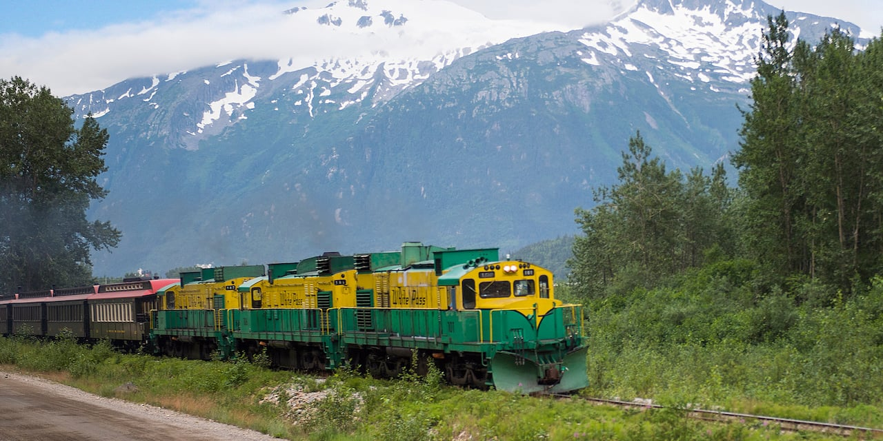 A train traverses the rails over the Alaskan terrain with a mountain range in the background