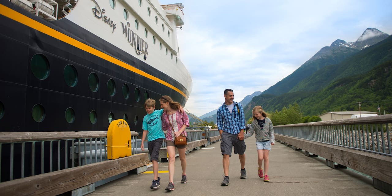 A family of 4 walk along a wood-plank road next to the Disney Wonder cruise ship with snow-capped mountains in the background