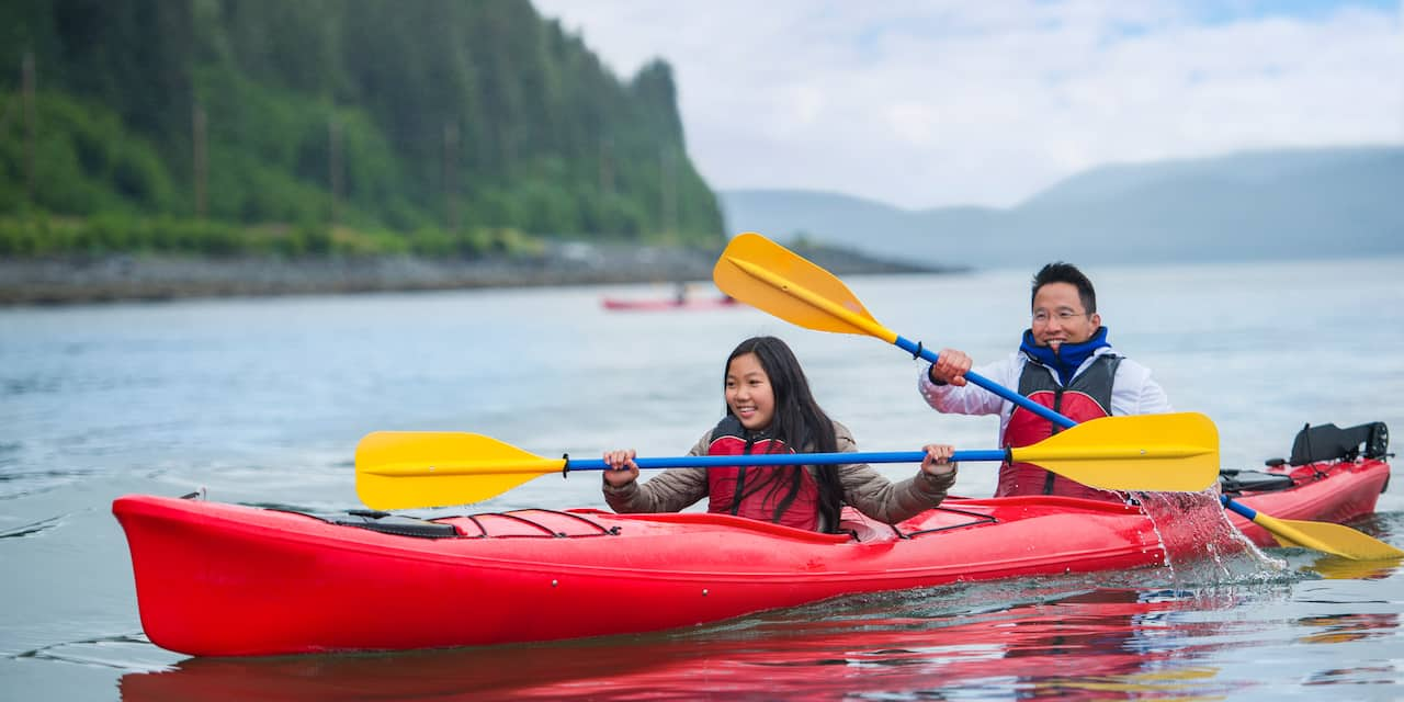 A father and his daughter paddle a 2-person kayak on Eklutna lake