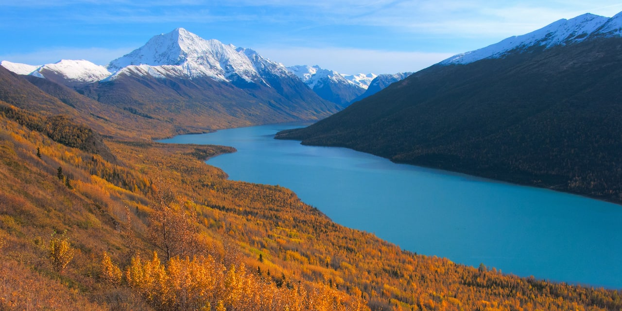 Blue Eklutna Lake nestled between snowy mountains