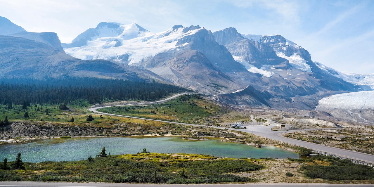 The snow-capped Canadian Rockies loom over the Columbia Icefield and a nearby valley with a lake