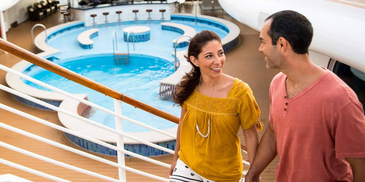 A couple hold hands as they ascend a stairway from a ship's deck with a pool and swim-up bar