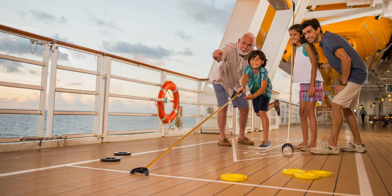 A family plays shuffle board on the deck of a ship