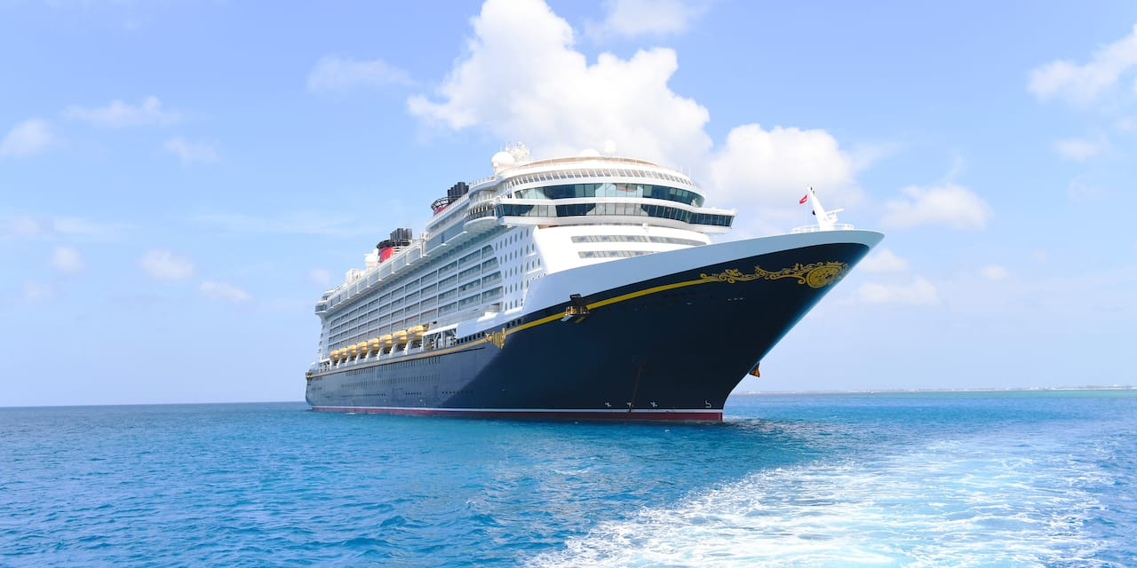 The <i>Disney Fantasy</i> cruise ship sails across the ocean waters beneath a cloud-dotted sky