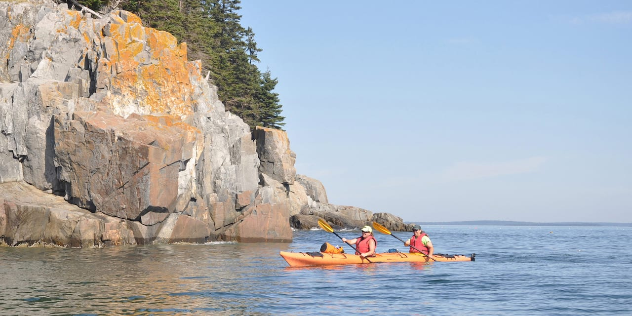 Two people paddling a two-person kayak near a rocky outcropping in a lake