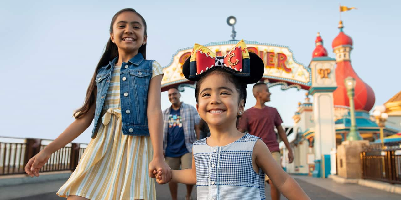 Two smiling girls, the smaller one wearing Micky Ears adorned with a Jesse Bow, hold hands as they exit Paradise Pier ahead of 2 older boys who walk behind them