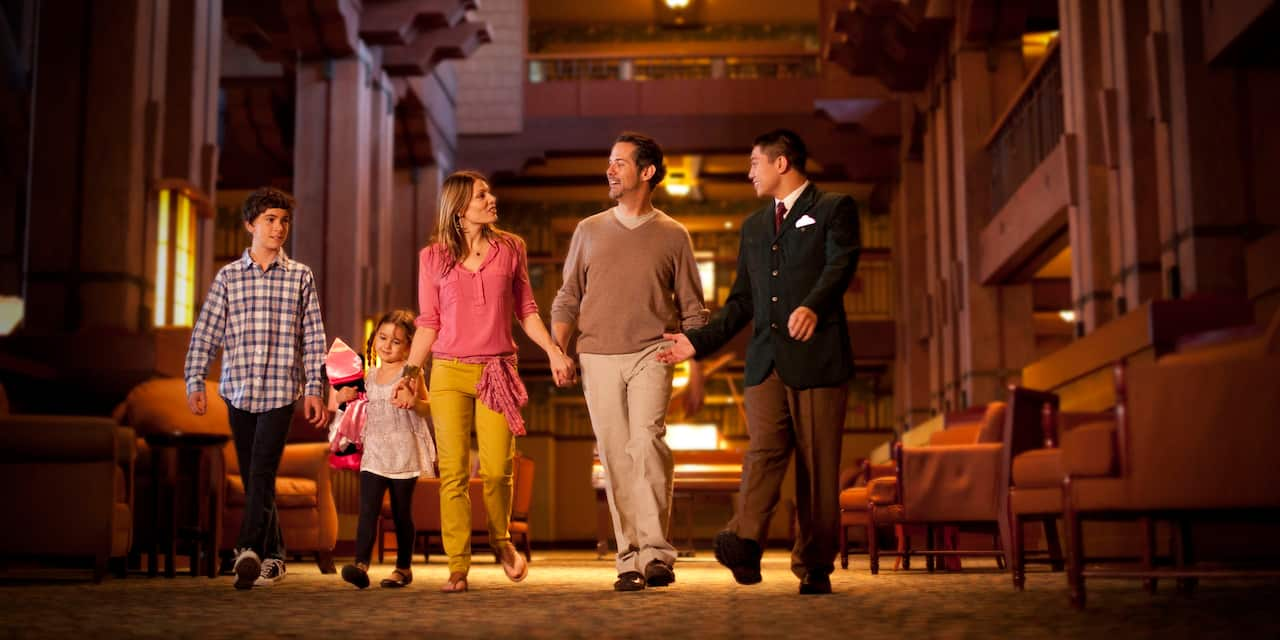 A male Cast Member leads a family of 4 through the lobby of Disney's Grand Californian Hotel & Spa at Disneyland Resort