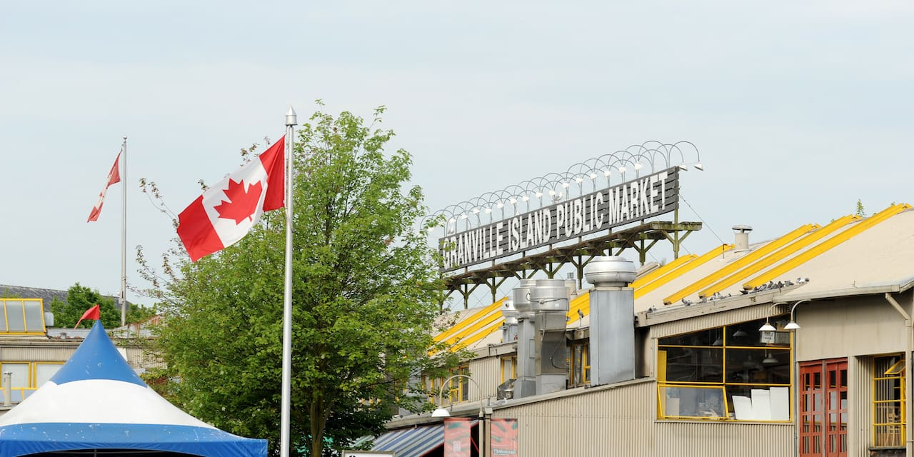 "A Canadian flag waves in front of a rooftop sign that reads, ""Granville Island Publilc Market"""