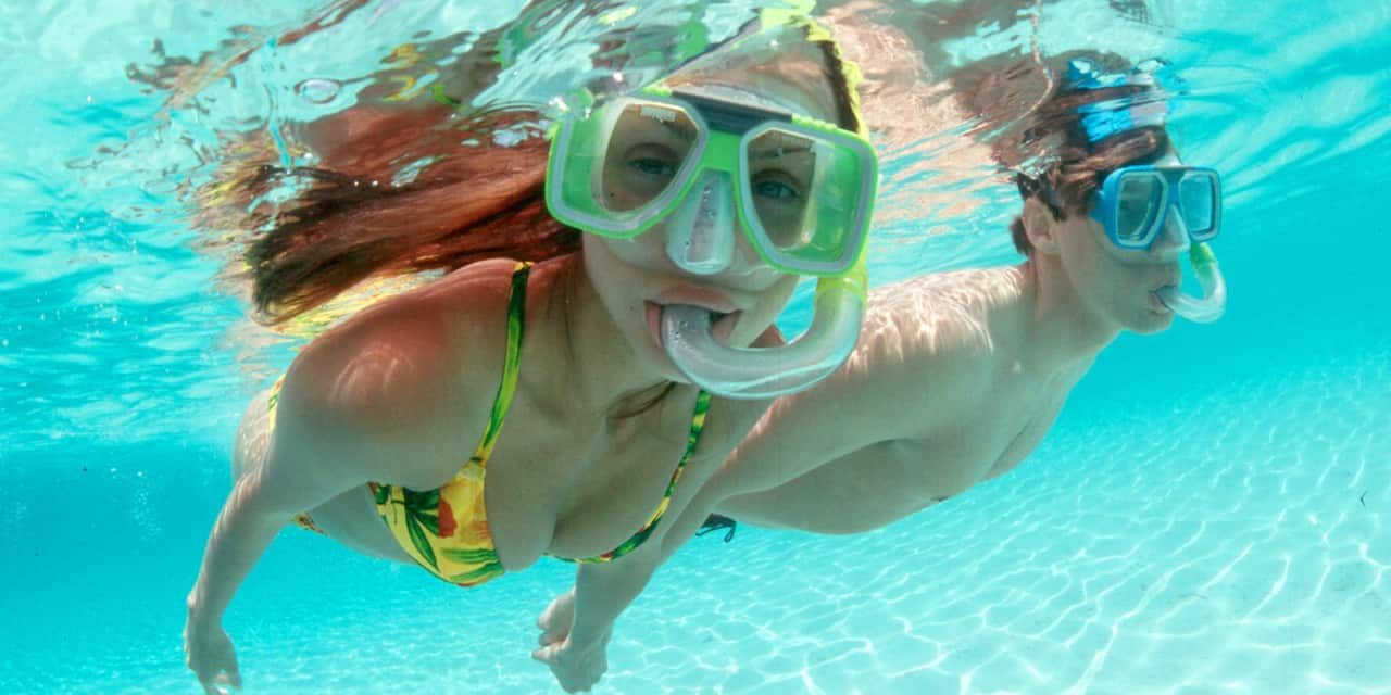 A couple wear masks and snorkels as they snorkel below the surface of the clear waters