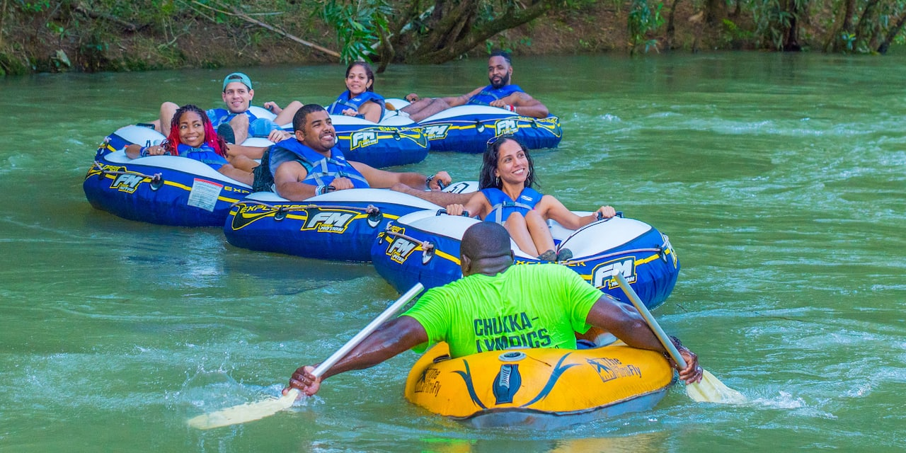 A guide faces a group of people on inner tubes he leads down a river
