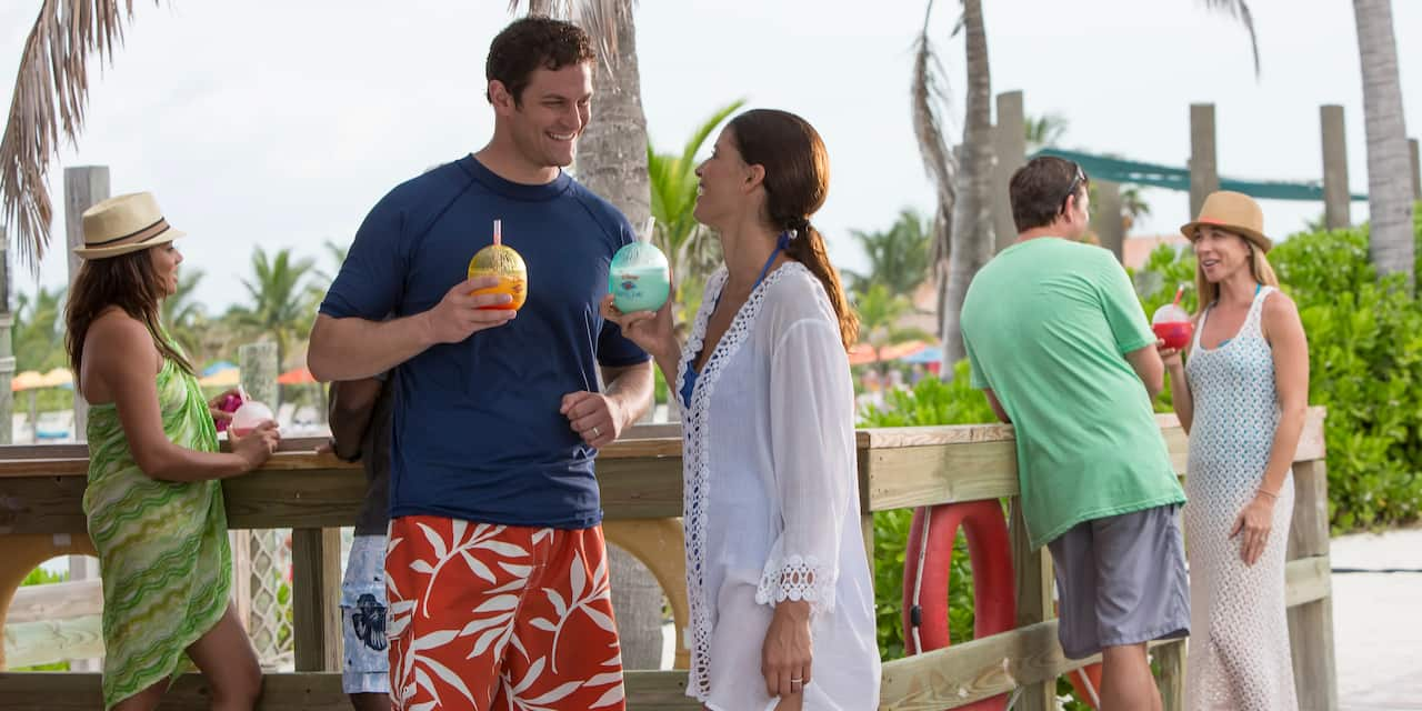 Several couples with tropical drinks have conversations near a wood railing with palm trees in the background