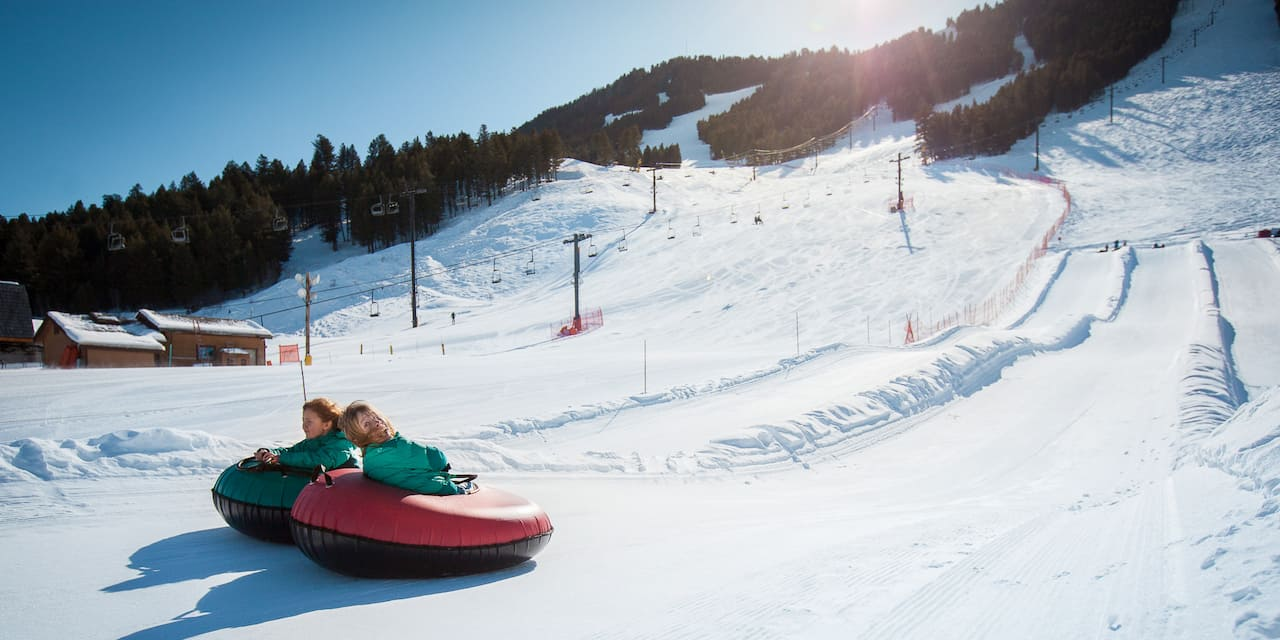 Two girls ride inner-tubes down a snowy track at Snow King Mountain in Jackson, Wyoming