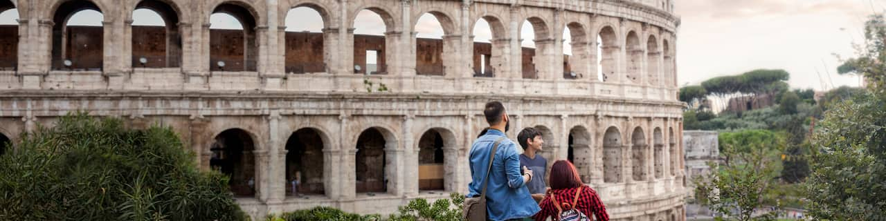 A family of 3 stands outside the Colosseum with its arched windows and stone exterior in Rome, Italy