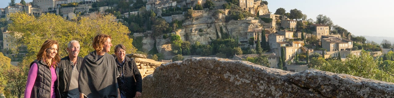A group of 4 people walk along a stone wall with the mountainside village of Les Baux-de-Provence, France in the background