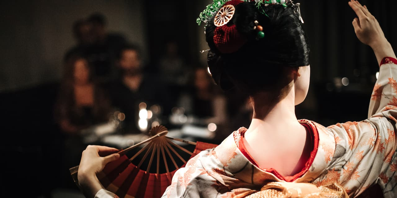 A Maiko in traditional dress with a fan performs