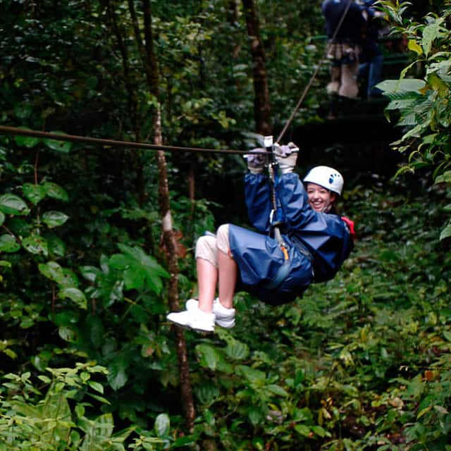 A young woman is all smiles as she zip lines through the rain forest