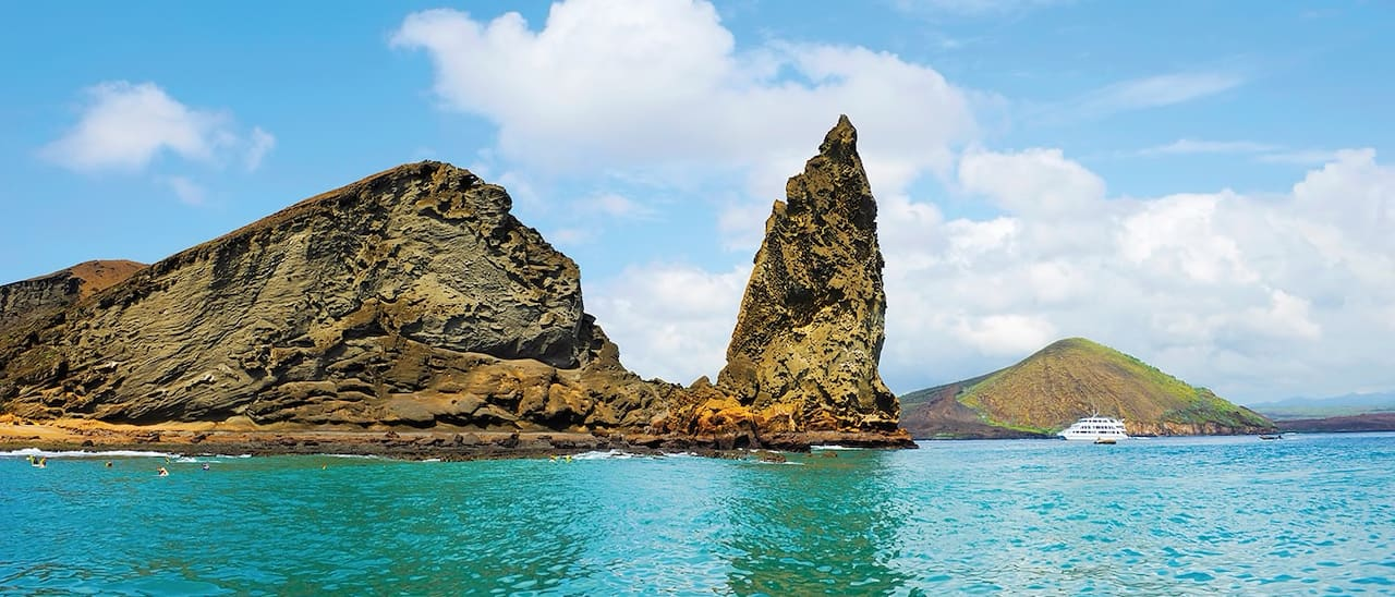 Two islands in the Galápagos, a rock formation on one and a boat coasting by the other