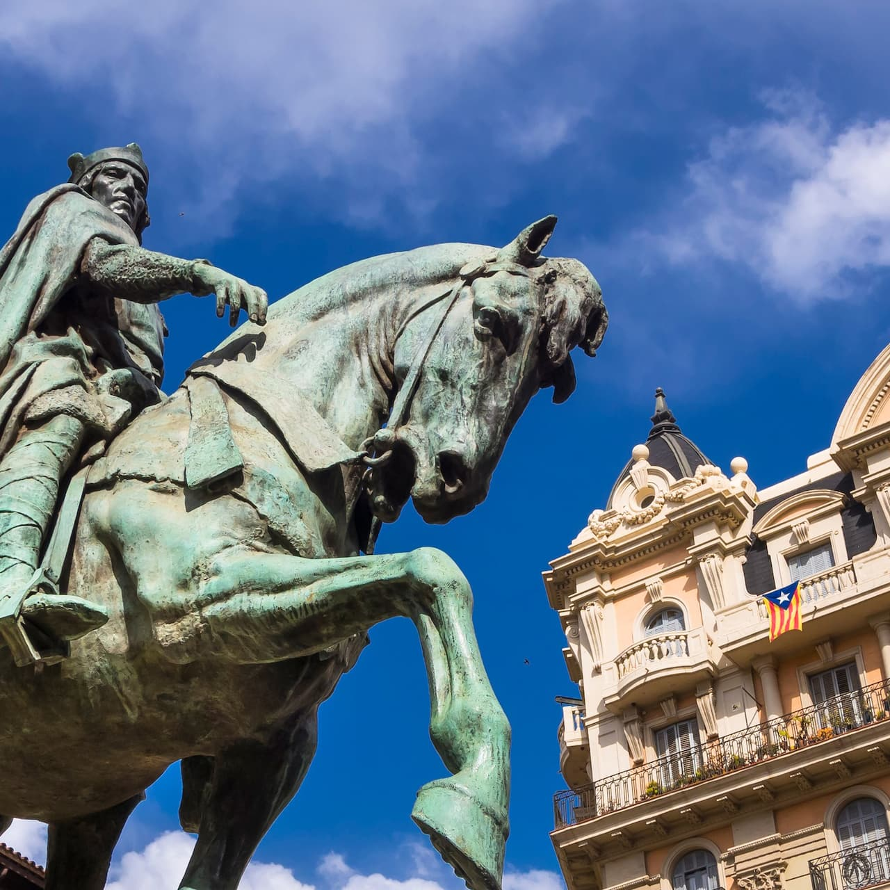 Statue of a man on a horse with classic buildings surrounding it