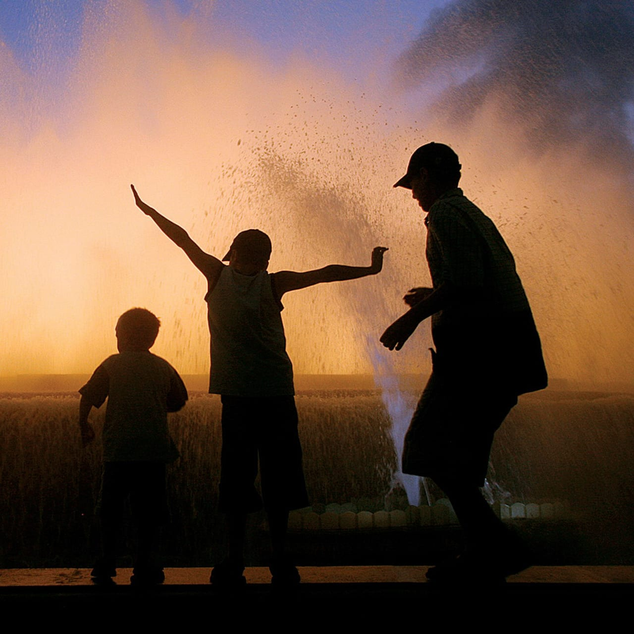 The silhouettes of 3 boys playing in front of a lighted fountain